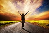 stock photo of stand up  - Happy woman standing with hands up on long straight road facing the sun - JPG