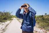 Man Hiking And Birdwatching And Looking Through Binoculars