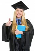 Happy Young Woman In Graduation Gown With Books Showing Thumbs U