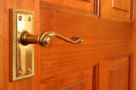 stock photo of door-handle  - brass handle on pine door - JPG