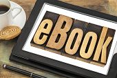 ebook (electronic book) - a word in letterpress wood type on a  digital tablet with a cup of coffee