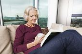 Senior woman reading book on sofa at home