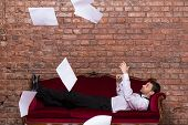 Businessman Lying On A Settee With Flying Papers