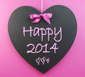Happy New Year 2014 Message Greeting Written On Heart Shape Blackboard Against A Pink Background.