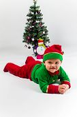 Baby Boy Dressed As Santa's Helper Lying Next To Christmas Tree.
