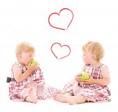 children and happiness concept - two adorable twins with apples over white