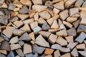 Background of dry chopped firewood logs in a pile