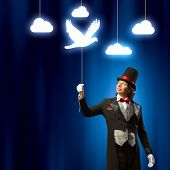 Image of man magician showing trick against color background