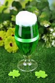 Glass of green beer for St Patricks day on grass close-up