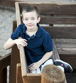 Handsome Young Boy Portrait In A Park On A Bench