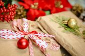 Ecologic gift wrap with kraft paper, red bow and christmas bauble