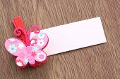 Pink Artificial Butterfly And Note Paper Stuck On Dark Wood.