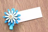 Blue Artificial Flowers And Note Paper Stuck On Dark Wood.