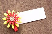 Red And Yellow Of Artificial Flowers And Note Paper Stuck On Dark Wood.