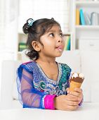 Little Indian girl licking her lips with an ice cream cone in hand, family living lifestyle at home.
