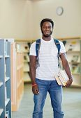 Portrait of confident young student with books standing in bookstore