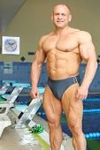 Happy sunburnt bodybuilder stands near indoor pool before swimming in gym hall