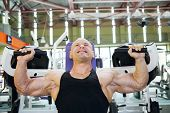 Bodybuilder in black jersey trains on exercise machine in gym hall
