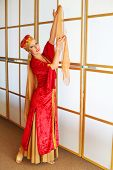 Pretty woman in red Andalusian costume poses with raised hands with shawls