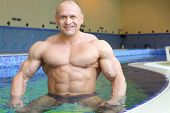 Happy bodybuilder stands in pure water of swimming pool of gym hall