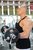 Serious bodybuilder in black jersey raises barbell in gym hall