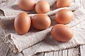fresh brown eggs closeup on linen background