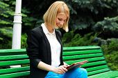 Young cheerful woman sitting on the street bench with tablet computer