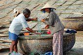 Muine, Vietnam - Feb 13, 2009: Vietnamese Fishermen Check Fishing Nets Near Round Wicker Boat (thung
