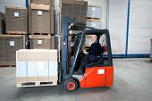 Forklift driving through a nice and clean warehouse. The experienced driver is transporting a pallet