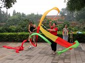 Beijing, China - Jul 17, 2011: Chinese Woman Doing Gymnastics With Ribbons In Jingshan Park. Tai Chi