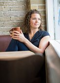 Thoughtful woman with coffee mug looking through window in cafeteria