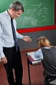 Happy mature male professor looking at little schoolgirl in classroom