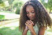 pic of evangelism  - Young girl praying in the park on a sunny day - JPG