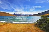 Lake in the high valley of the Patagonian Andes. The sharp strong wind drives the waves with white f