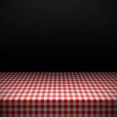 Table covered with red checkered tablecloth. Vector.