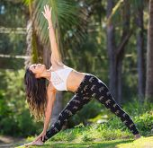 Young woman practicing yoga outdoors. Healthy natural lifestyle.