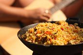 Dish with Afghan Plov with guitar playing guy background