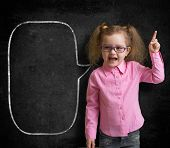 Funny child in eyeglasses standing near school chalkboard  as a teacher with blank speech bubble ske