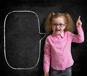 Funny child in eyeglasses standing near school chalkboard  as a teacher with blank speech bubble sketch.