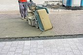 picture of grout  - Worker with machine grouting compound street paved with bricks - JPG