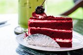 stock photo of red velvet cake  - Red velvet cake on foil at the bottom with cherry on top - JPG