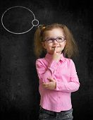 Funny child in eyeglasses standing near school chalkboard and thinking