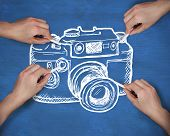 Composite image of multiple hands drawing camera with chalk against navy blue