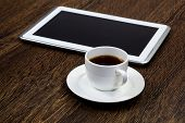 Tablet pc cup of coffee standing on wooden table