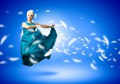 Young attractive woman in blue dress jumping high