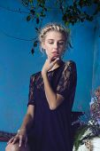 Beautiful blond woman with braid hairstyle and natural makeup. Wearing lace black dress. Against grunge blue background