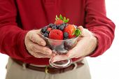 Closeup of senior man's hands holding a bowl of healthy, antioxidant rich berries.