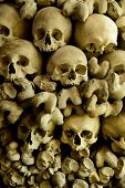 stock photo of peculiar  - Human skulls and bones in the wall of the Skull Chapel in Czermna - JPG