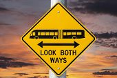 Look both ways bus and tram warning sign with sunset sky.