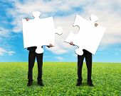 stock photo of comrades  - Two men holding blank puzzles on grass ground with blue sky - JPG